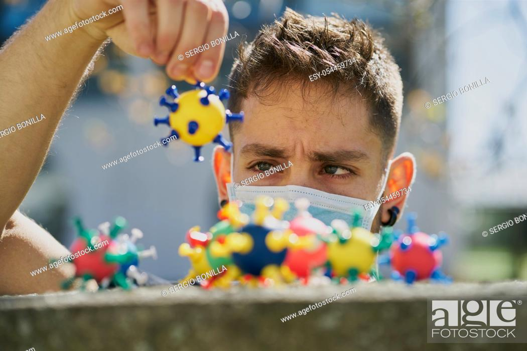 Stock Photo: Caucasian man with a protective mask and catching virus models. The concept of Coronavirus.