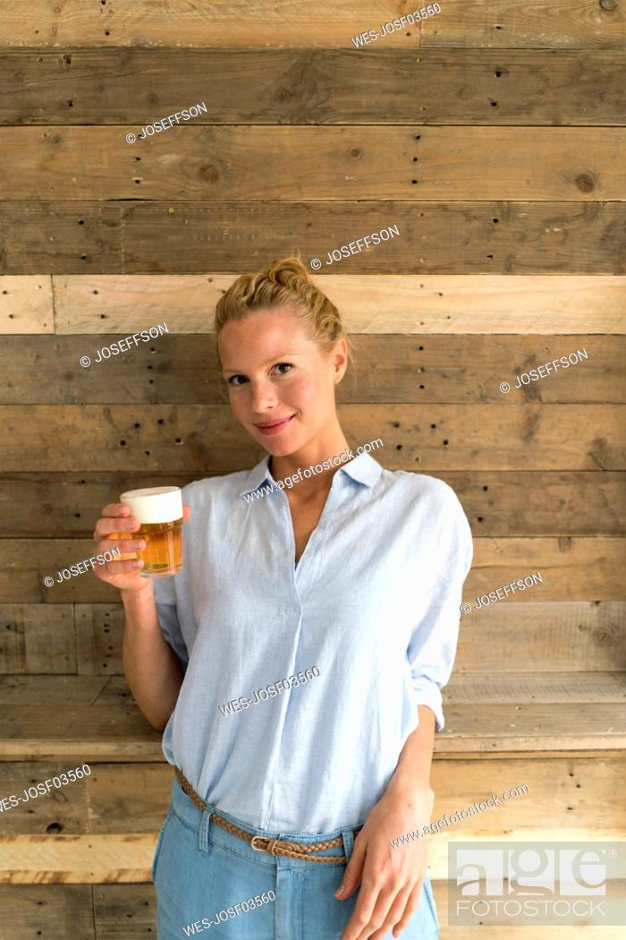 Stock Photo: Portrait of blond woman with a glass of beer.