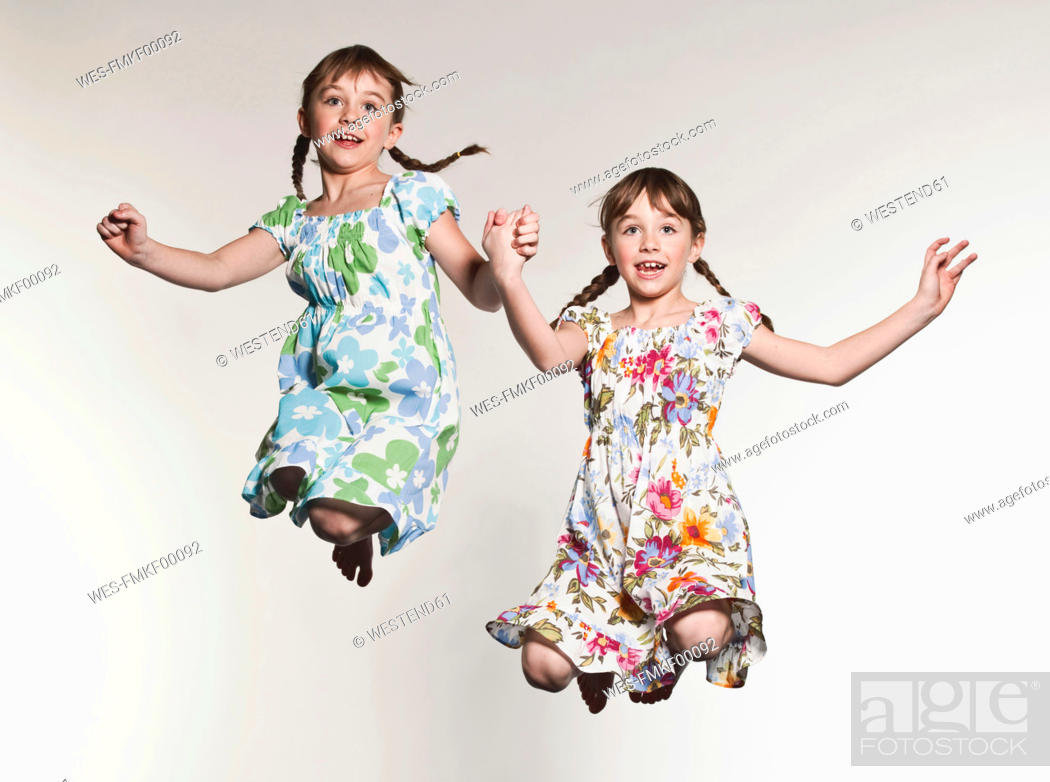 Stock Photo: Girls 6-7 holding hands and jumping, smiling.