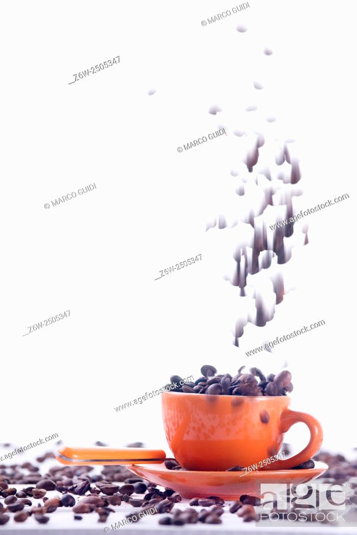 Imagen: Cup of coffee on orange background with white beans.