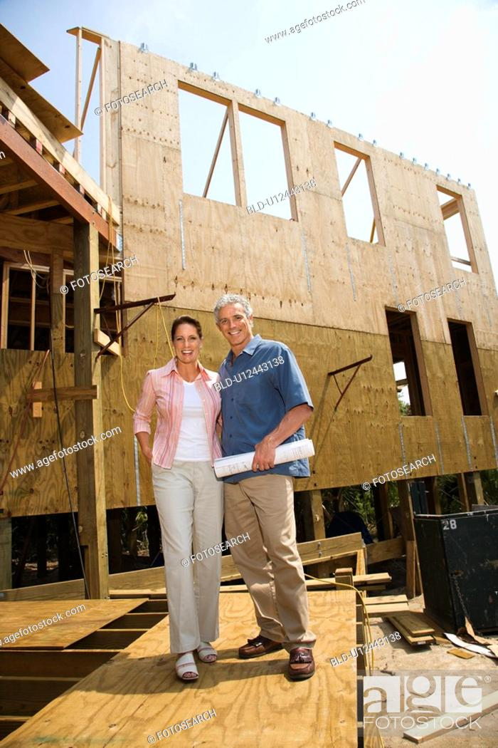 Stock Photo: Caucasian mid-adult male holding blue prints with arm around mid-adult female in building construction site.