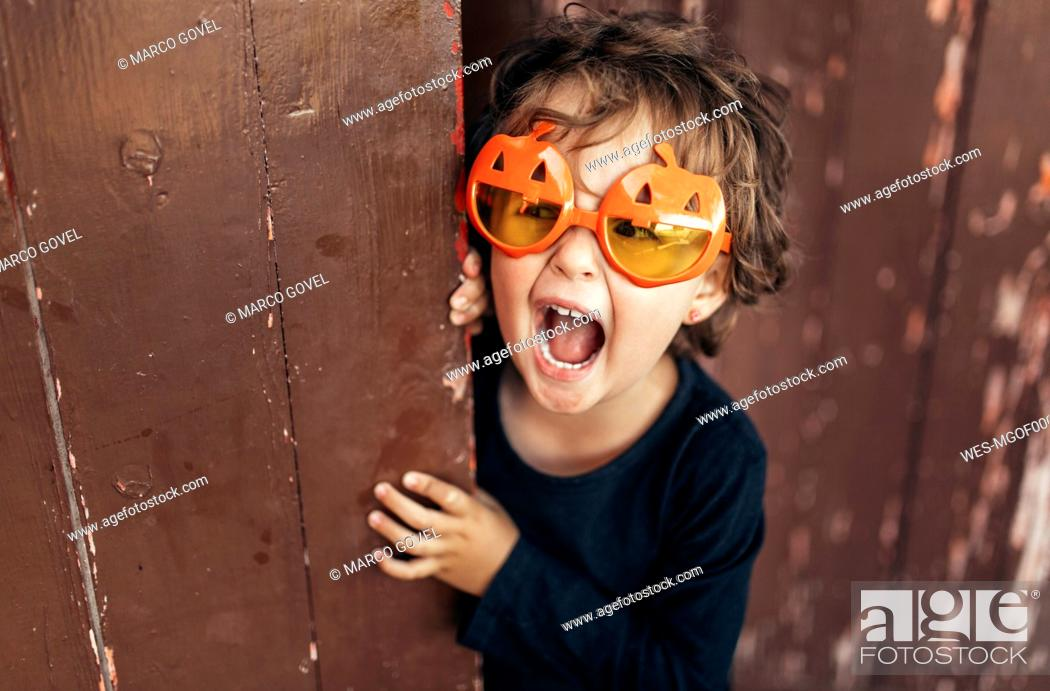 Stock Photo: Portrait of little screaming girl wearing halloween glasses shaped like pumpkins.