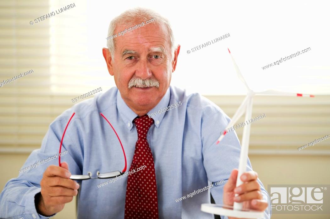 Stock Photo: Senior eco engineer projecting new areas with wind turbines.