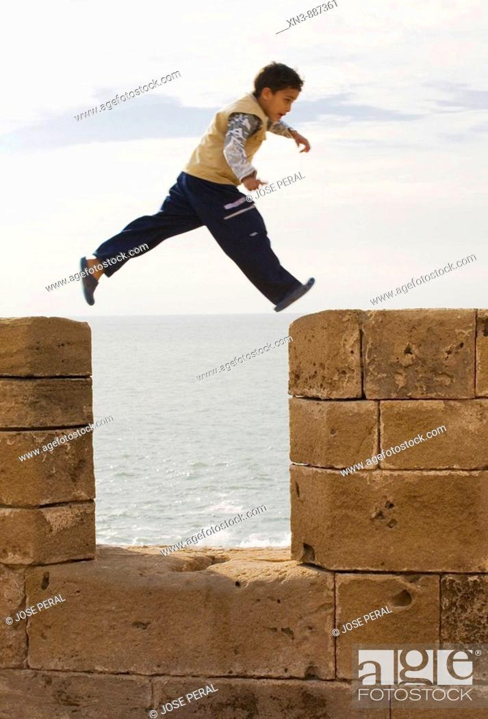 Stock Photo: Boy jumping on the wall of Essaouira, Marocco.