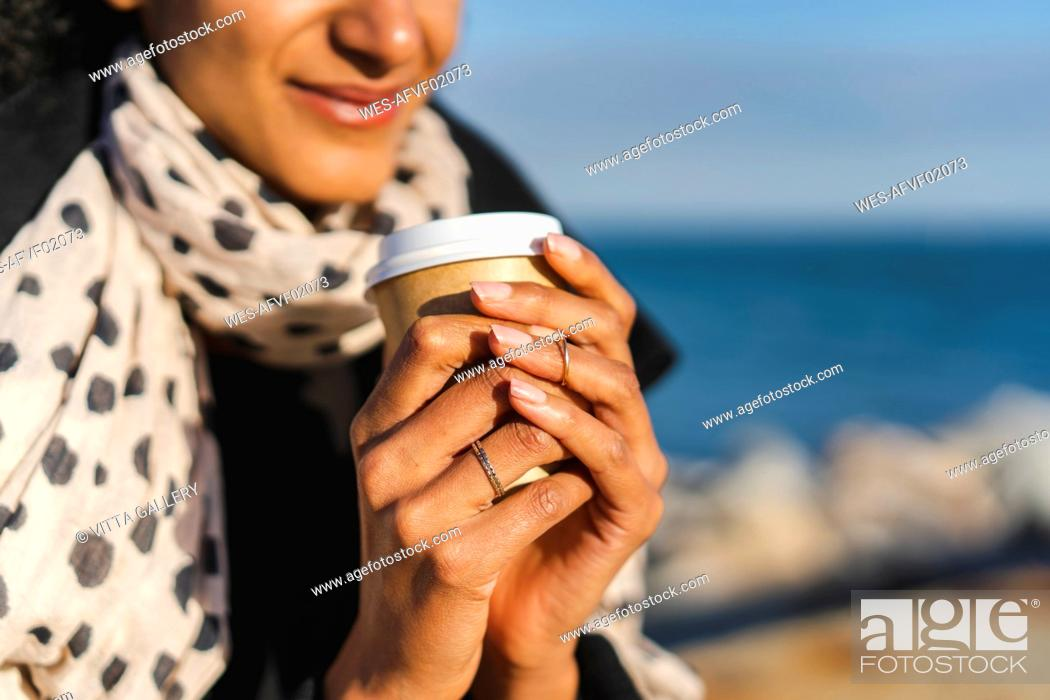 Photo de stock: Woman's hands holding coffee to go, close-up.