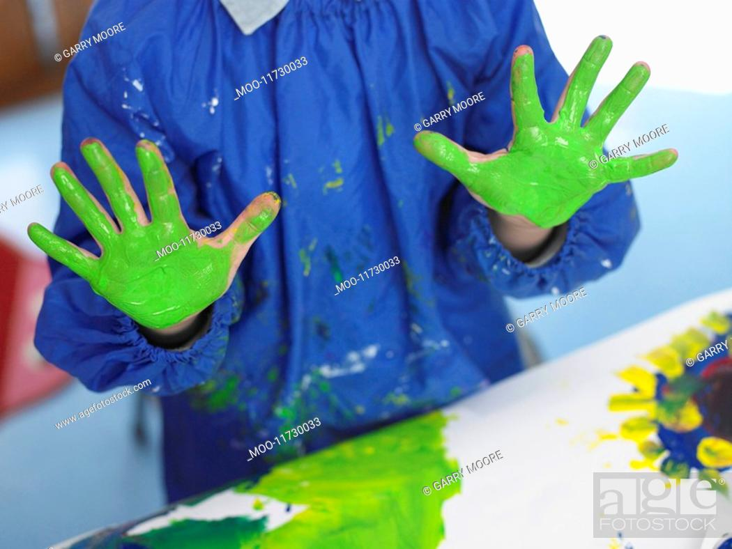 Stock Photo: Boy finger painting in art class mid section.