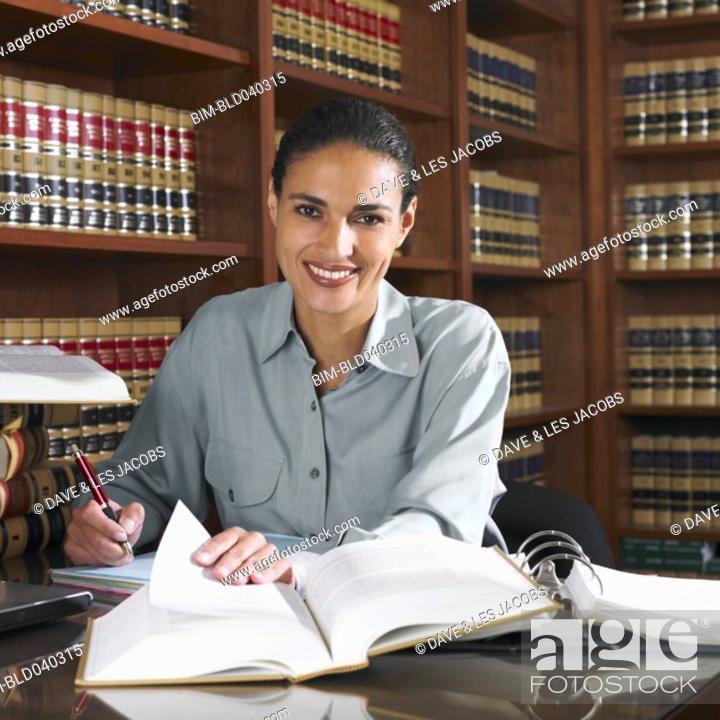 Stock Photo: Hispanic female lawyer working in office.