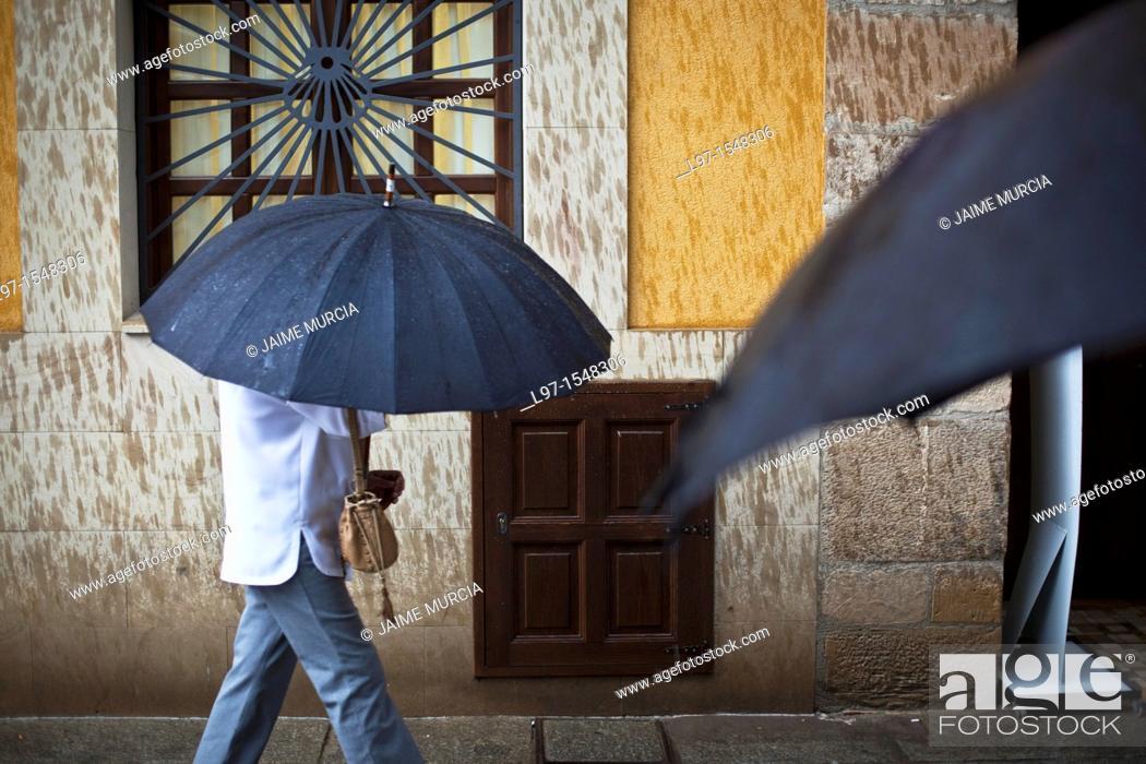 Stock Photo: Two black umbrellas in a village street.