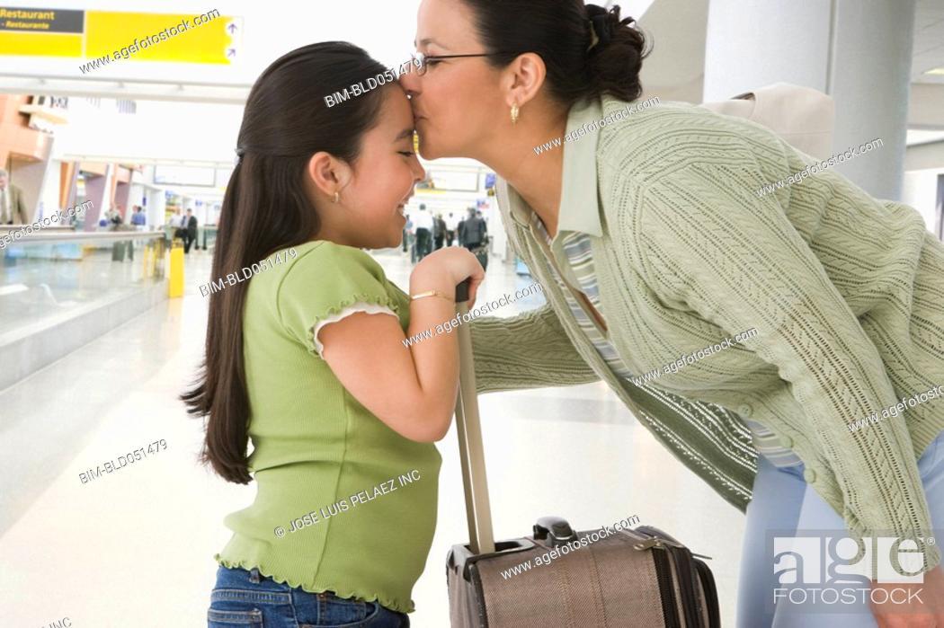 Stock Photo: Hispanic grandmother kissing granddaughter on forehead.