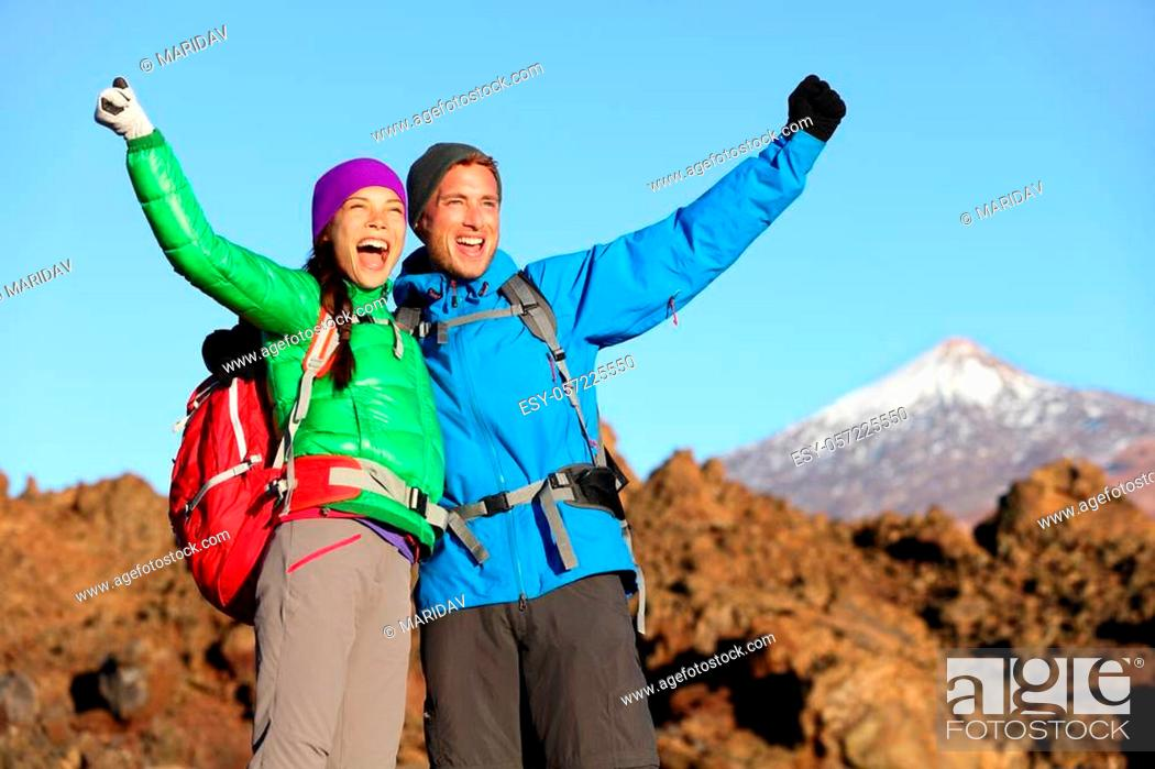 Imagen: Happy celebrating winning hiking people at top. Cheering hiker couple enjoying freedom on hike with arms raised in mountain landscape.