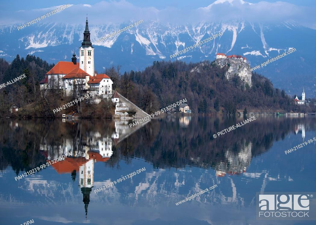 Stock Photo: 19 February 2021, Slovenia, Bled: The Church of the Assumption of the Virgin Mary on the island of Blejski Otok in Lake Bled at the foot of the Pokljuka plateau.