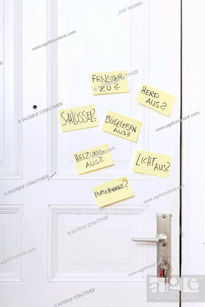 Stock Photo: Adhesive notes on a front door with various reminders in German.