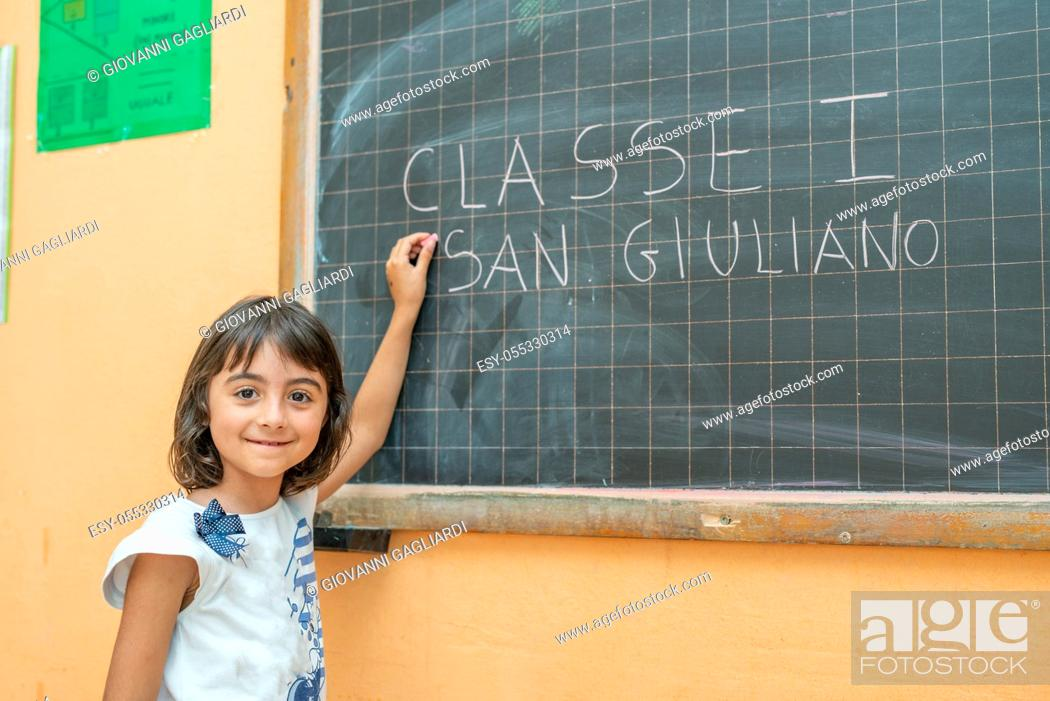 Stock Photo: Young girl on her first day of elementary school in the classroom writing on the chalkboard.