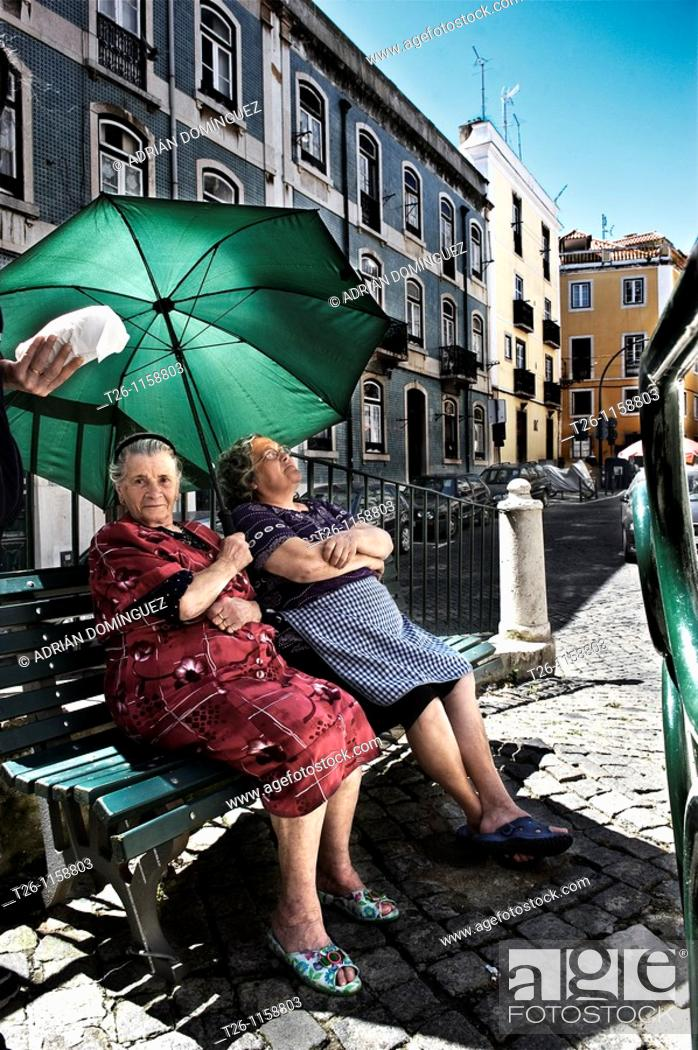 Stock Photo: two women sitting in the shade in the Alfama district. Lisbon, Portugal.