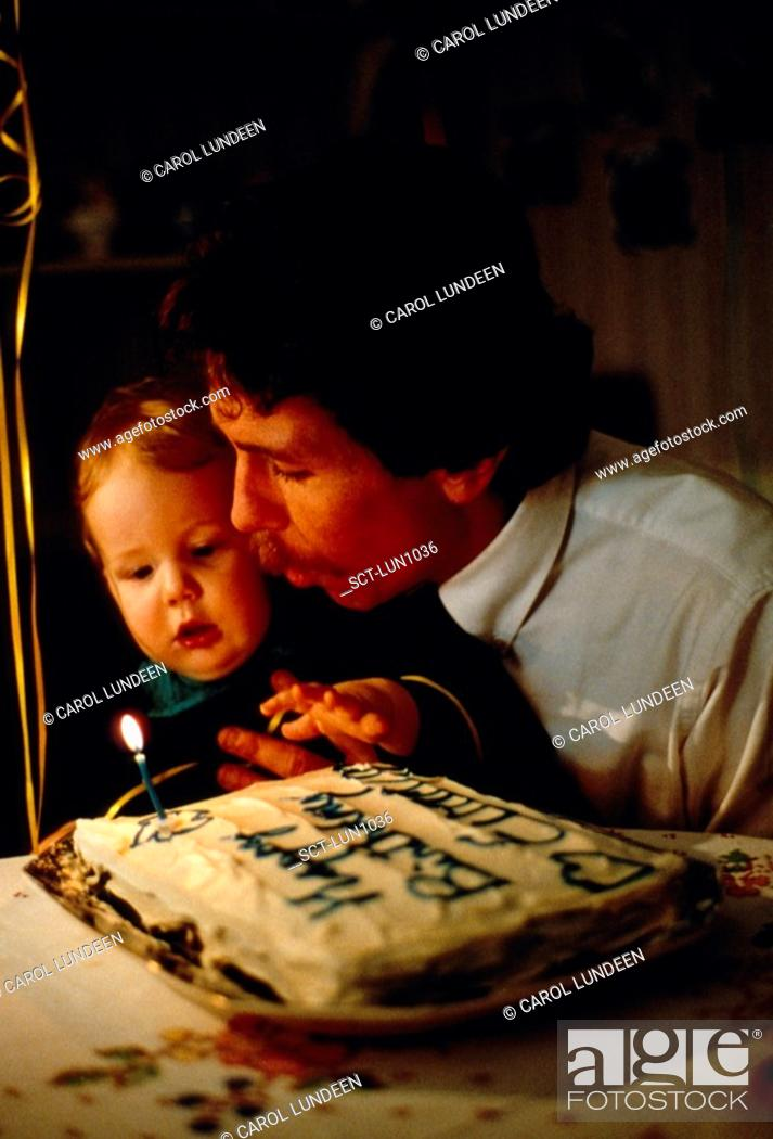 Stock Photo: Father helps his one-year-old son blow out the candles on his first birthday cake.