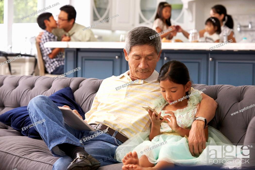 Stock Photo: Grandfather And Granddaughter Using Mobile Phone At Home.