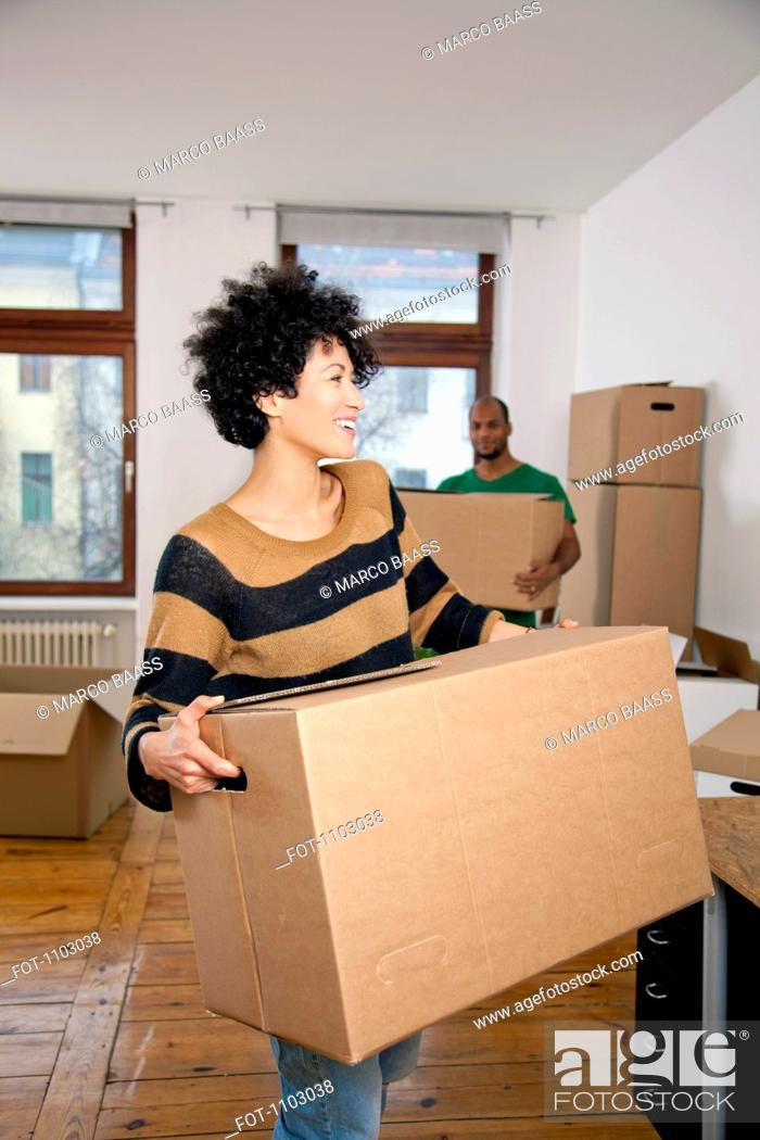 Stock Photo: A man and woman carrying moving boxes, focus on woman.