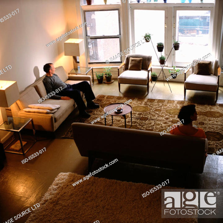 Stock Photo: Couple sitting apart in living room.