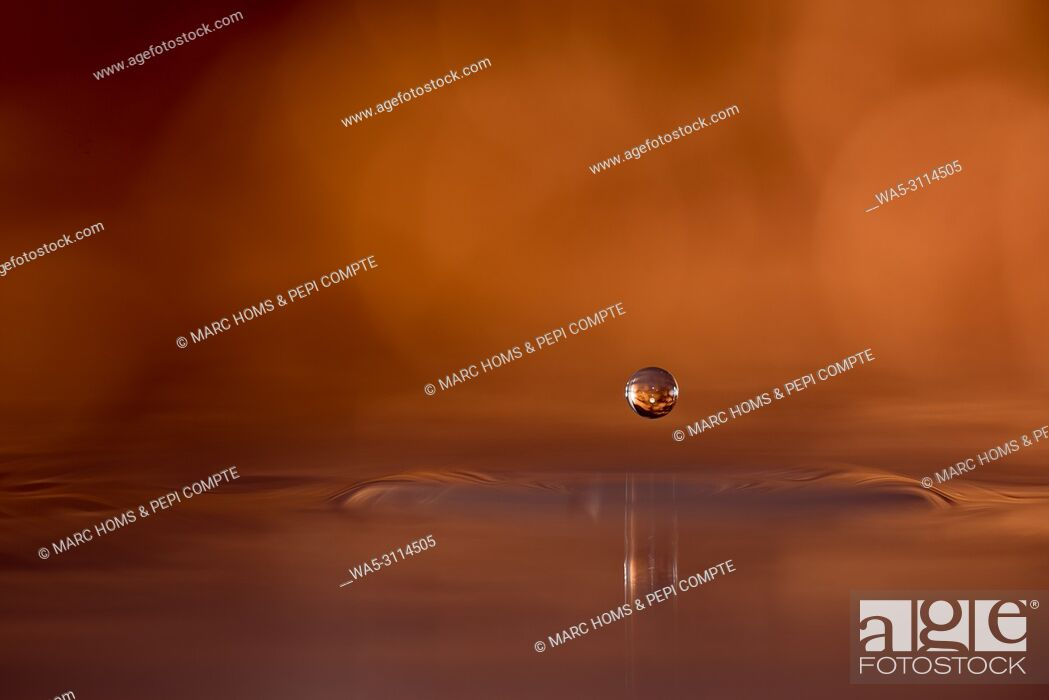 Stock Photo: Copper colored water drop suspended above the surface of the water.