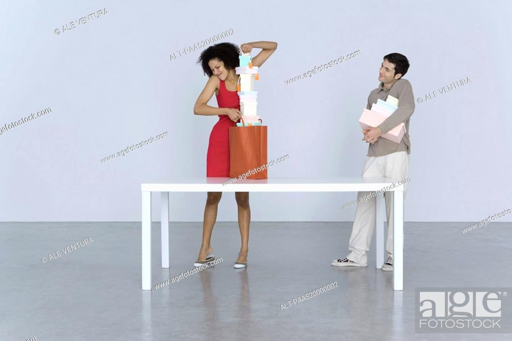 Stock Photo: Woman shoving large stack of boxes into shopping bag, man standing nearby with more boxes.
