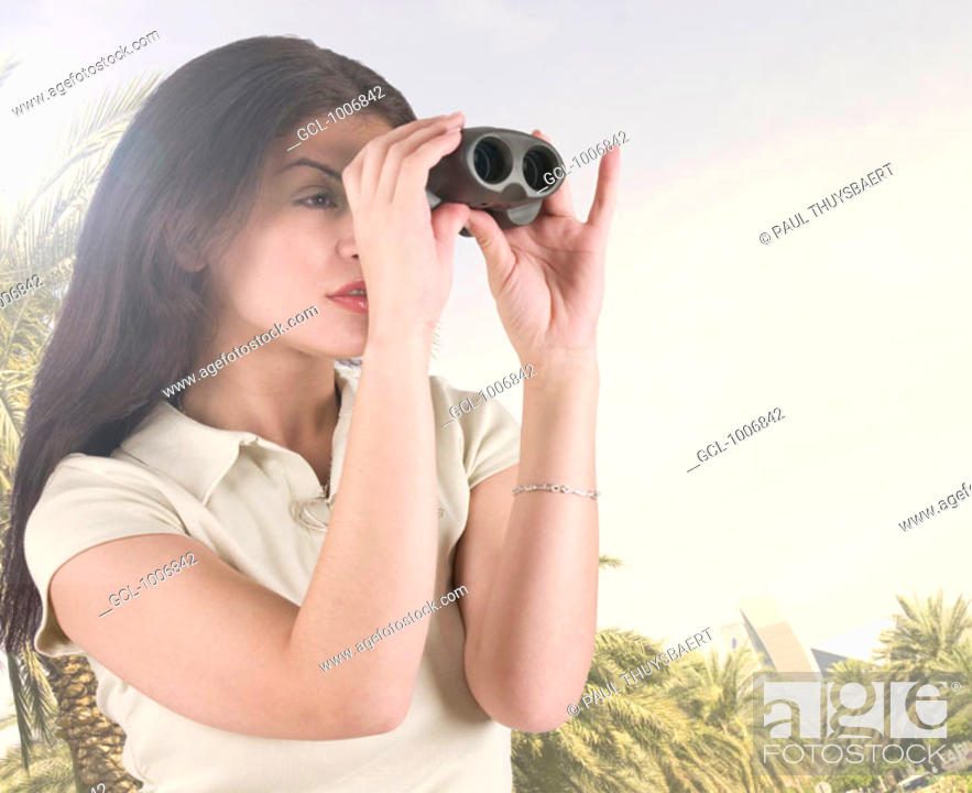 Stock Photo: Arab tourist looking through binoculars at Dubai landmarks.