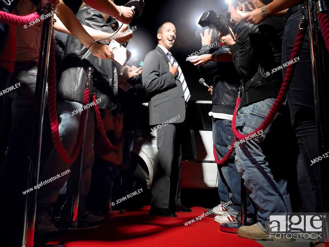 Stock Photo: Man on red carpet in front of paparazzi.