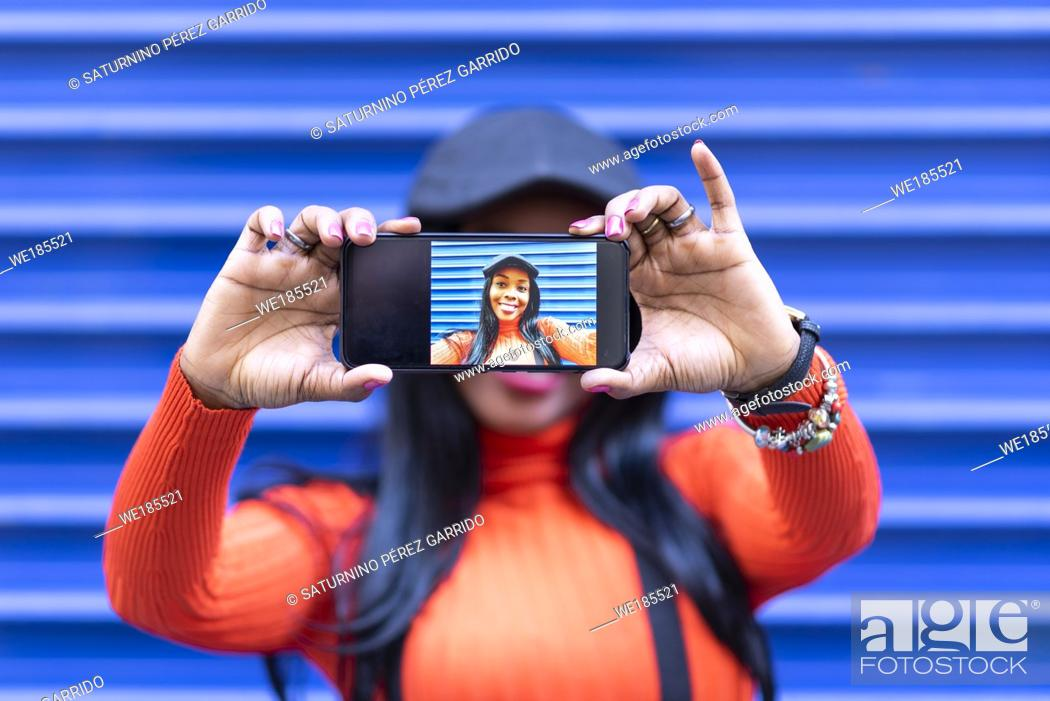 Stock Photo: Pretty young girl smiling and making herself a self-portrait.
