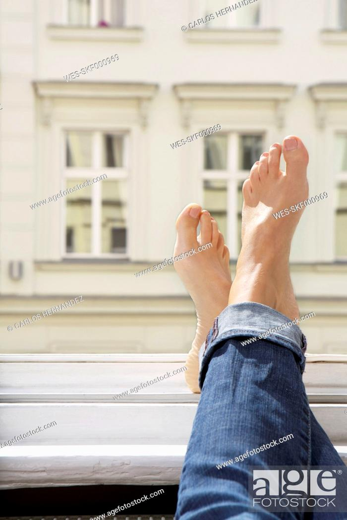 Stock Photo: Germany, Berlin, Young woman feets on open window.