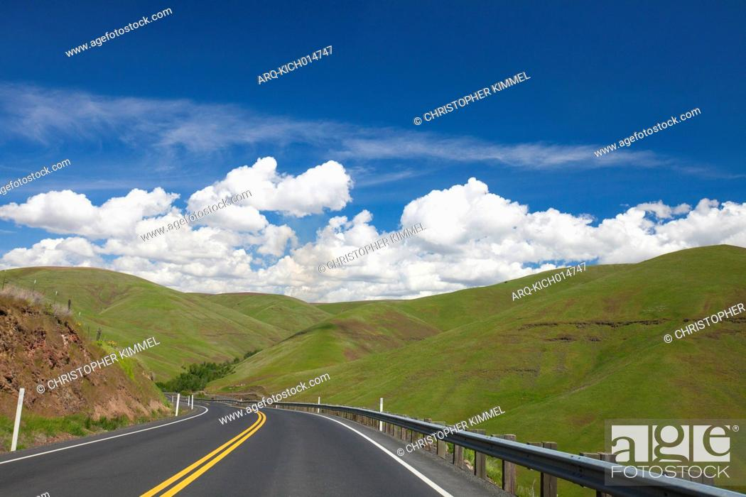 Stock Photo: Scenery of country road and green rolling hills under blue sky with clouds, Palouse, Washington State, USA.