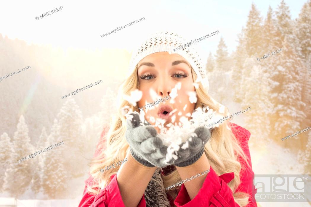 Stock Photo: Young woman blowing snow off from hands.