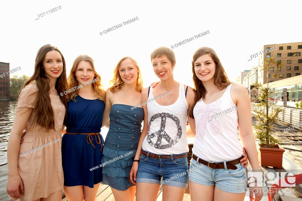 Stock Photo: Five cheerful young female friends standing a row, Spree River, Berlin, Germany.