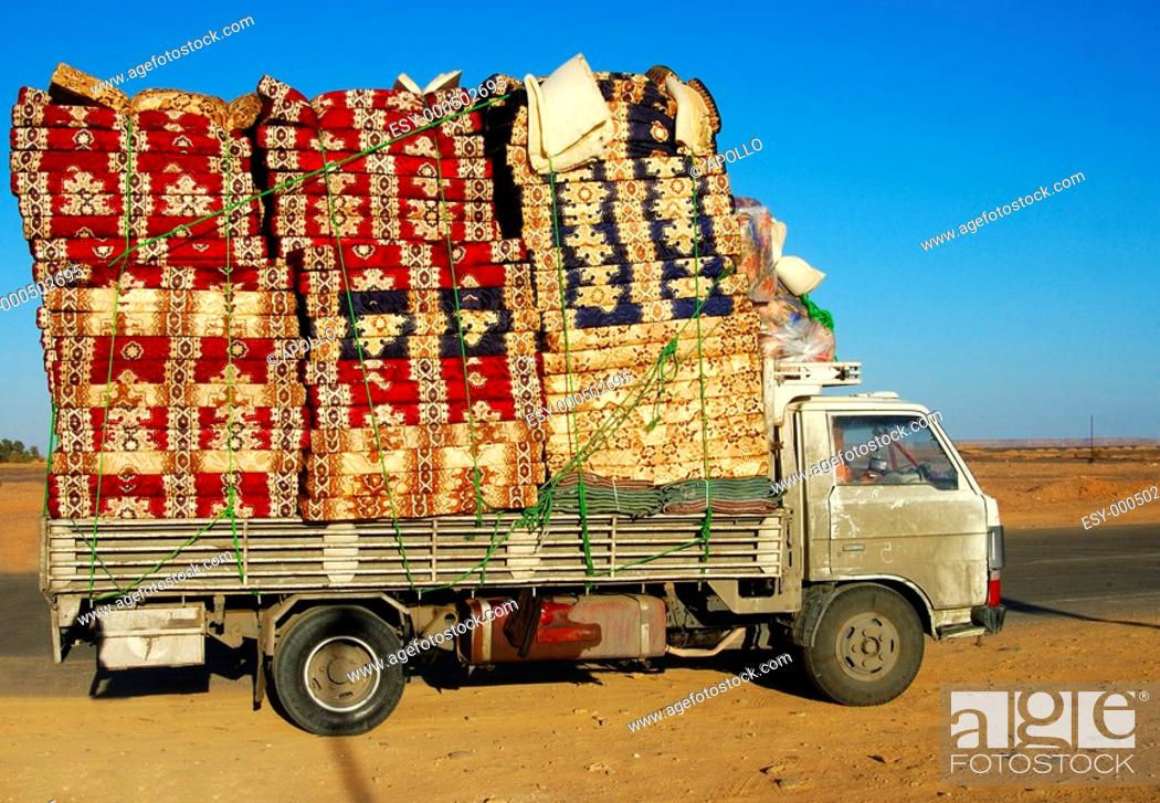 Stock Photo: Pick-up with a piling load of mattresses, Libya.