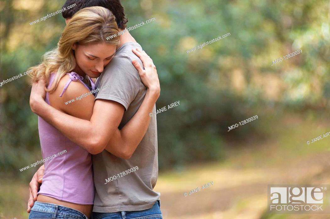 Stock Photo: Couple standing on forest trail Hugging side view.