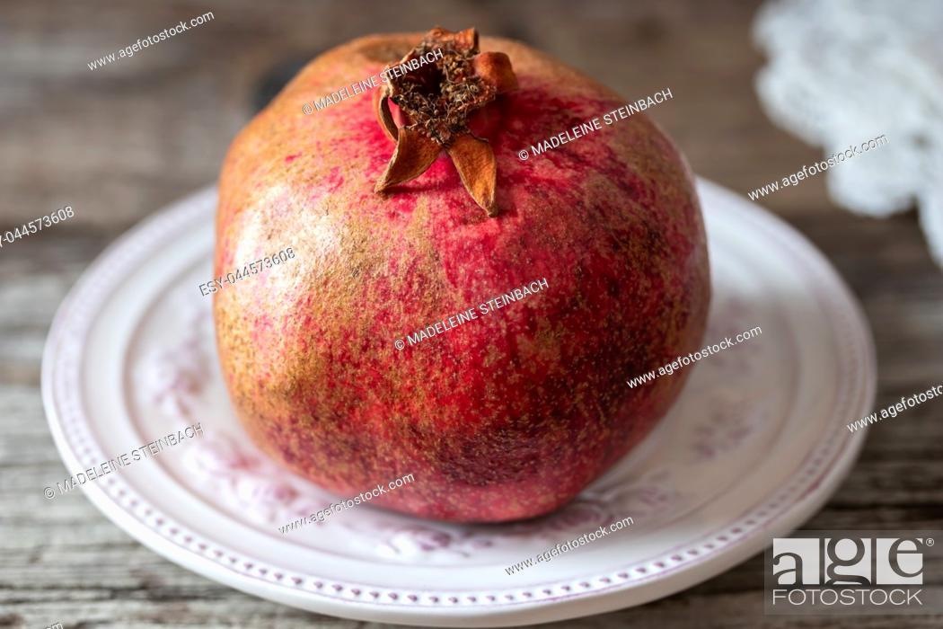 Stock Photo: Fresh pomegranate on a vintage plate.