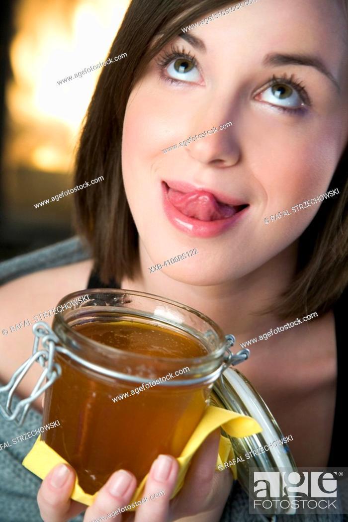 Stock Photo: woman eating honey.