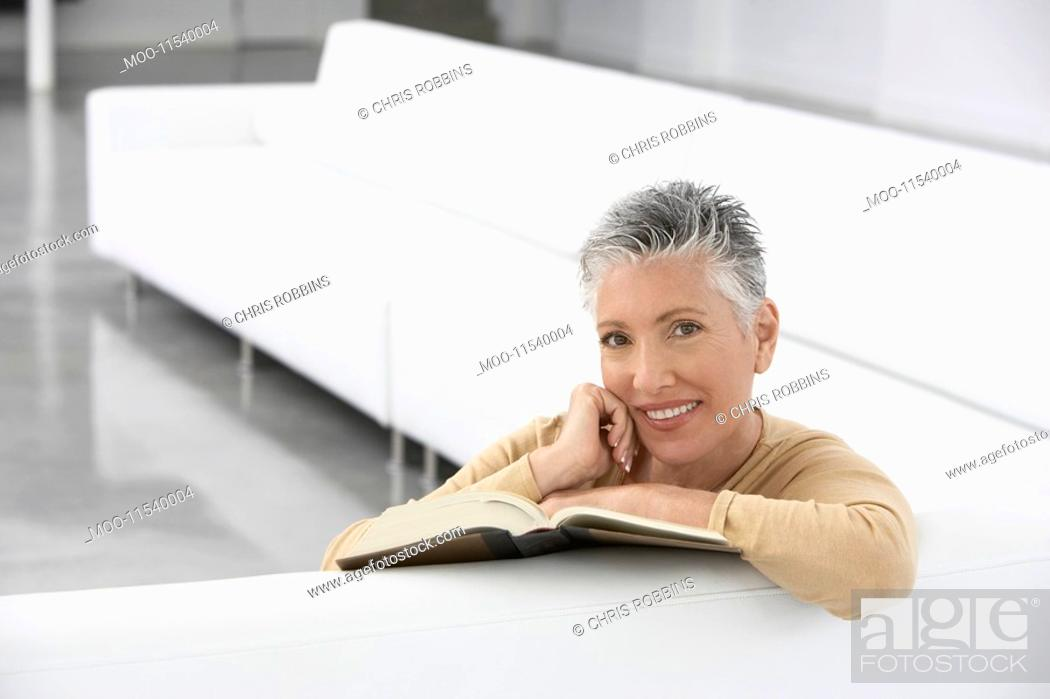 Stock Photo: Woman with book on sofa smiling portrait.