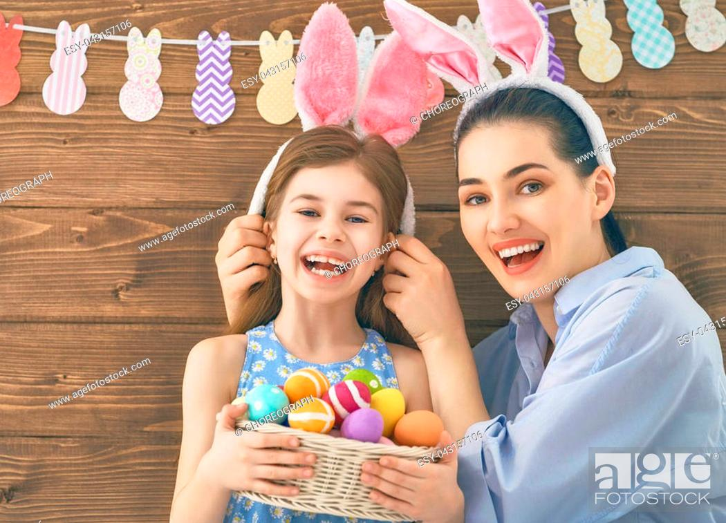 Photo de stock: Happy holiday! Mother and her daughter with painting eggs. Family preparing for Easter. Cute little child girl is wearing bunny ears.