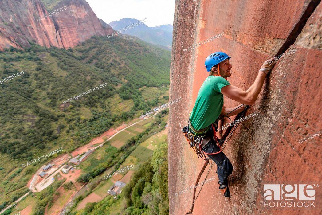 Stock Photo: Rock climber scaling rock face, Liming, Yunnan, China.
