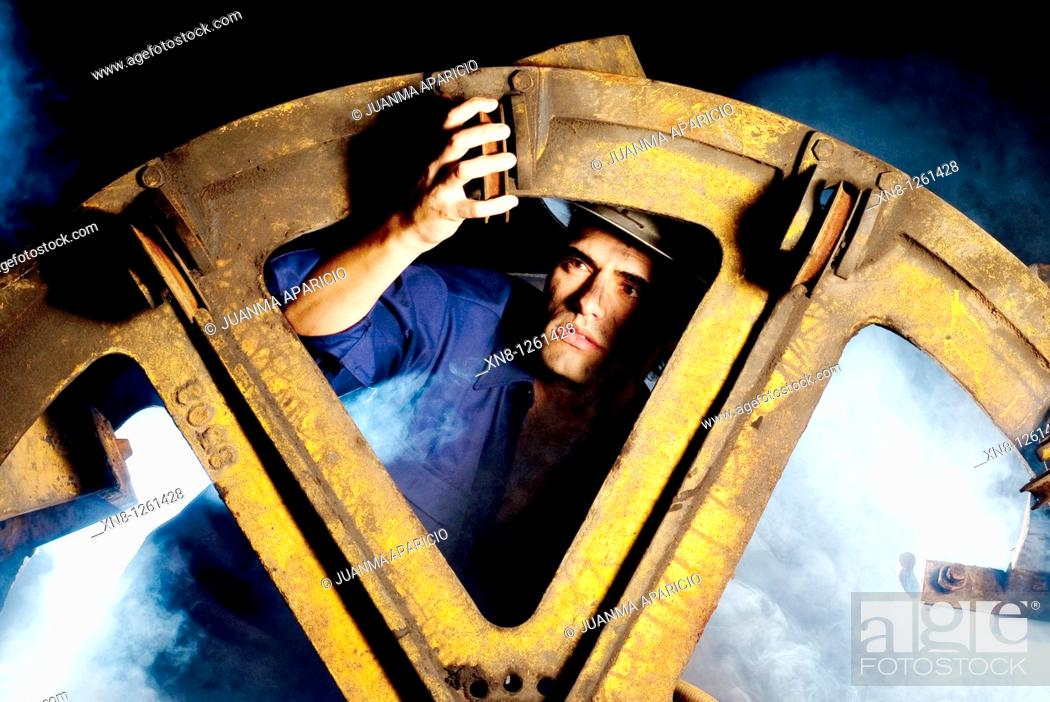 Stock Photo: Workers repairing a large pulley on the inside of a mine when shooting with.
