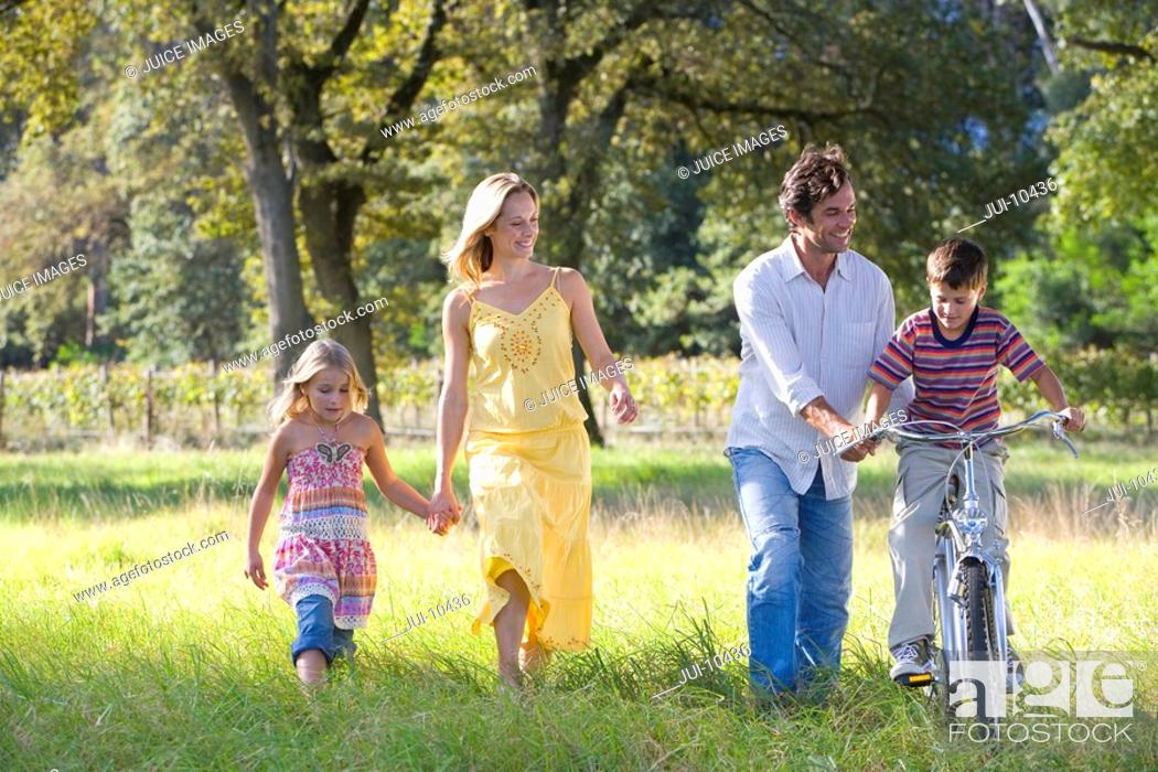 Stock Photo: Family of four in field, father helping boy 6-8 on bike, smiling.