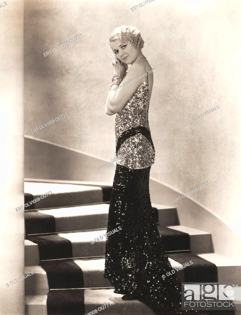 Stock Photo: Woman in sequined gown standing on staircase.