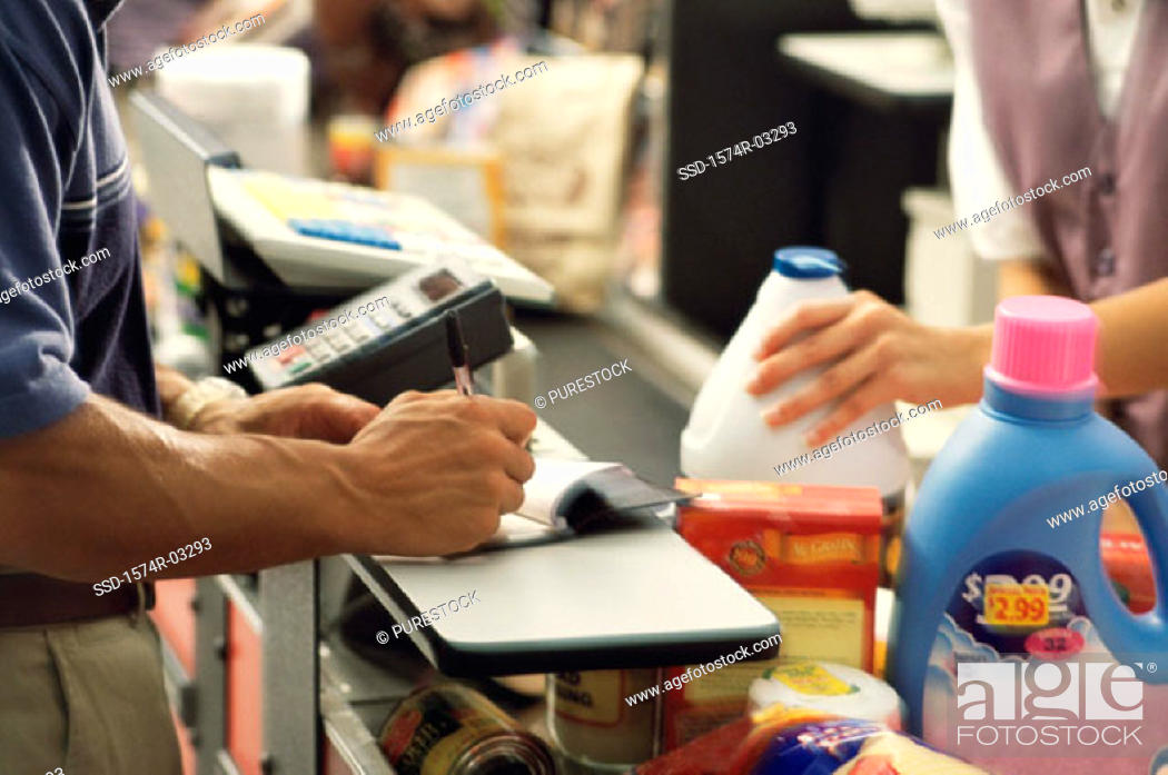 Stock Photo: Mid section view of a man and a woman at a checkout counter in a supermarket.