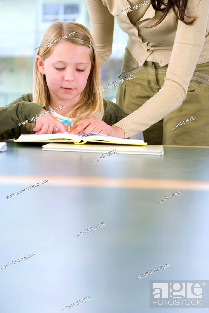 Stock Photo: Mother helping daughter 7-9 with homework.