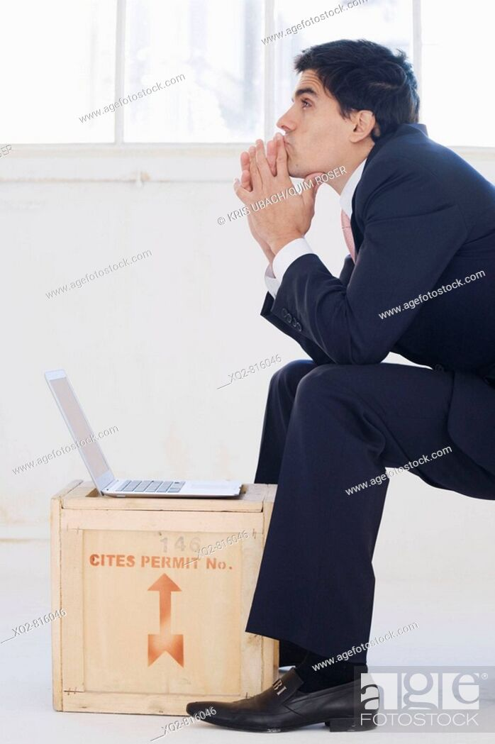 Stock Photo: Businessman working on latop on crate.