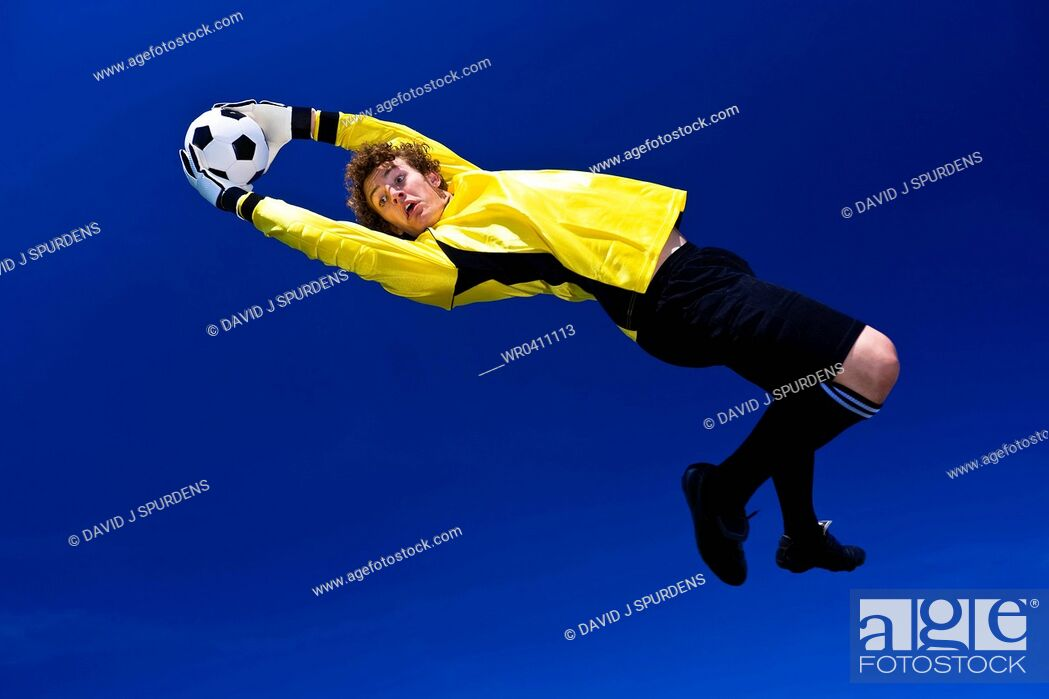 Stock Photo: A goalkeeper stretches to make the save.