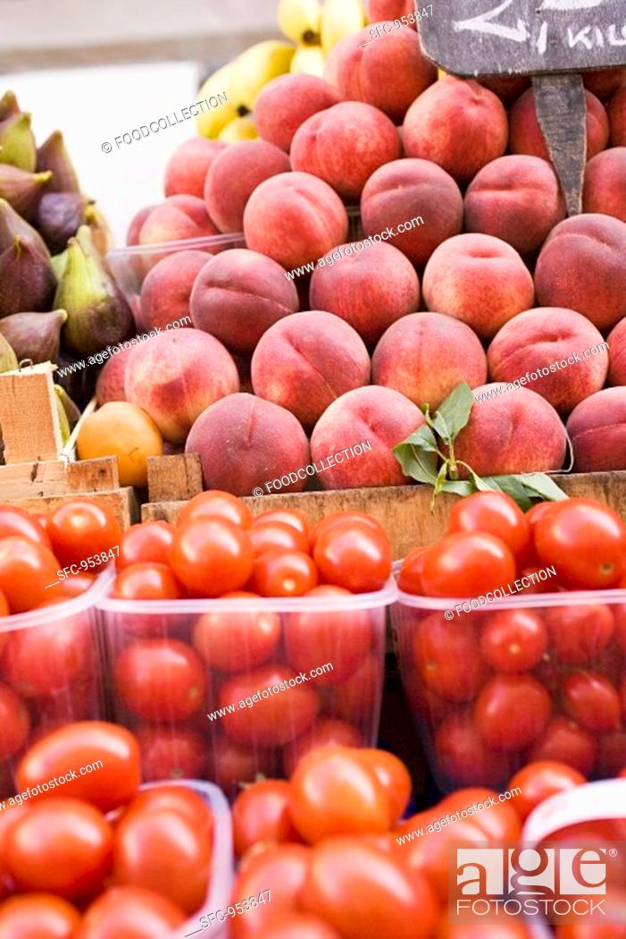 Stock Photo: Tomatoes and peaches at a market.