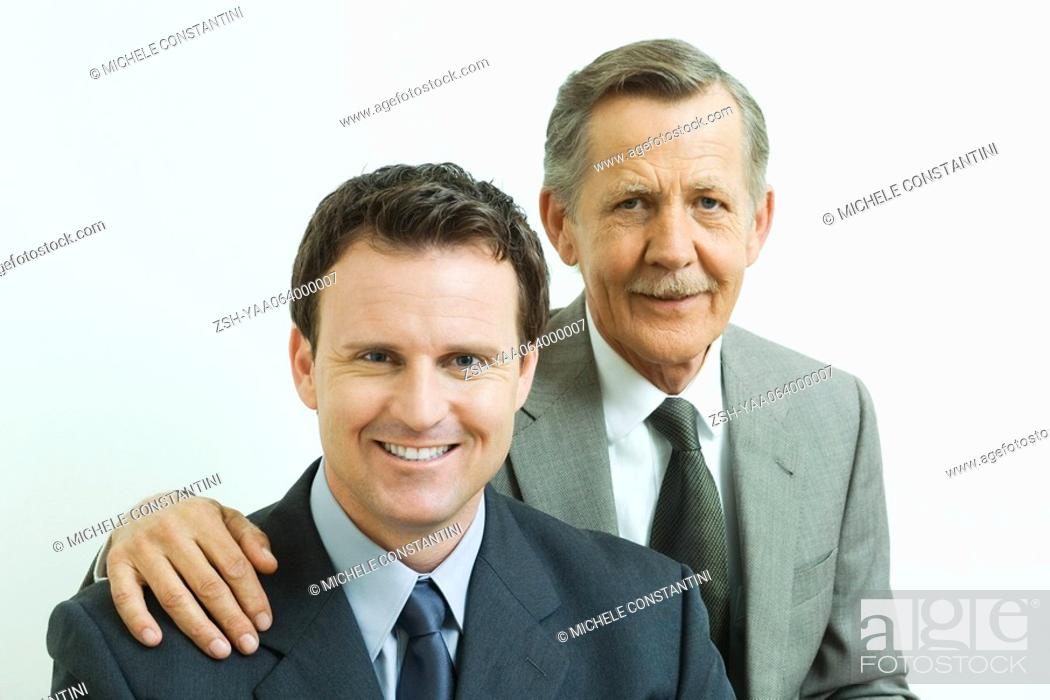 Stock Photo: Businessman with hand on associate's shoulder, both smiling at camera, portrait.