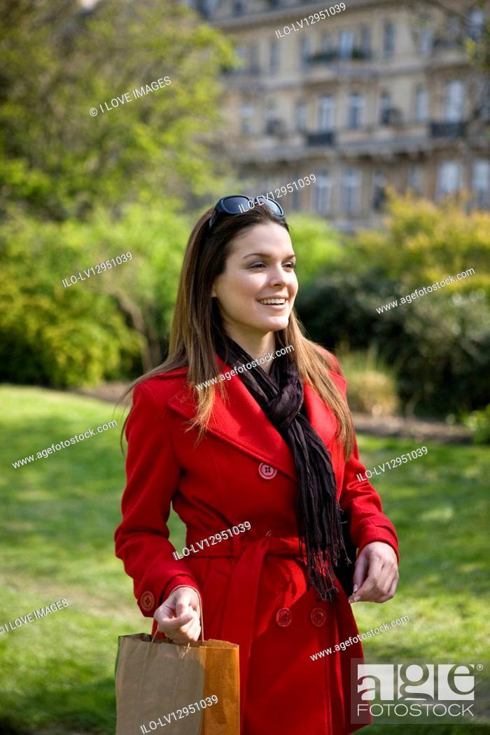 Stock Photo: A young woman walking, carrying a shopping bag.