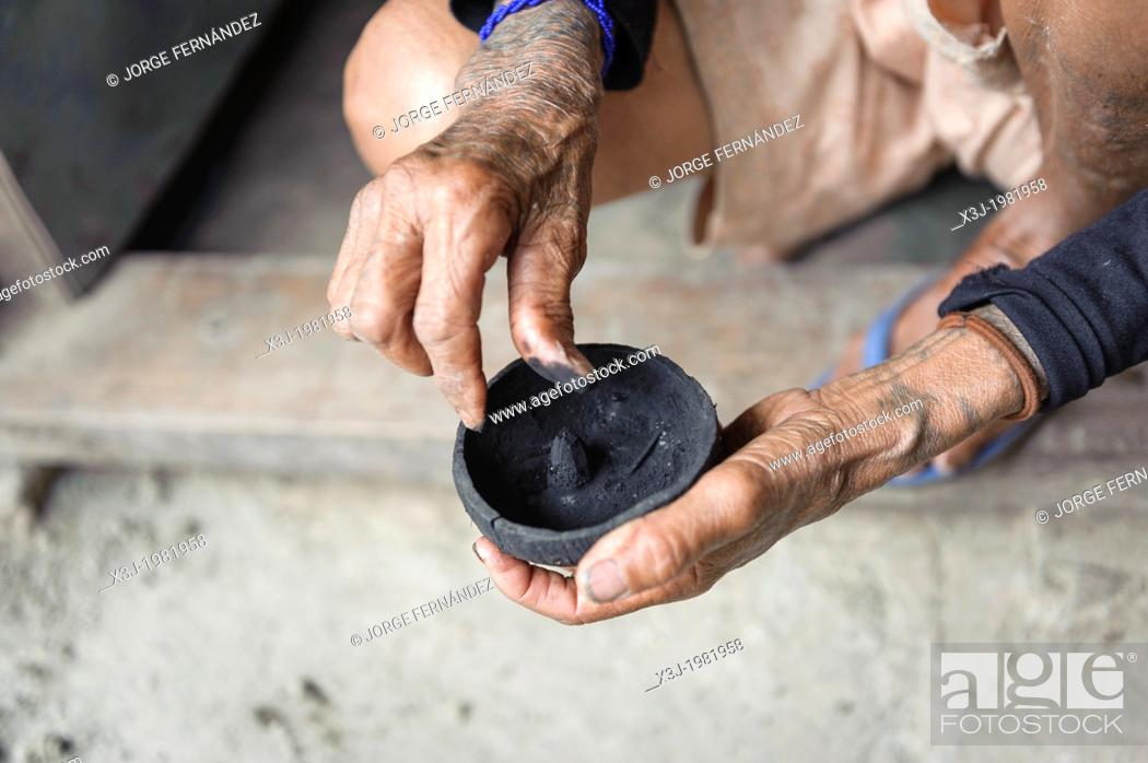 Stock Photo: Woman preparing a mixture to make a tattoo in a traditional way, Kalinga, Philippines.
