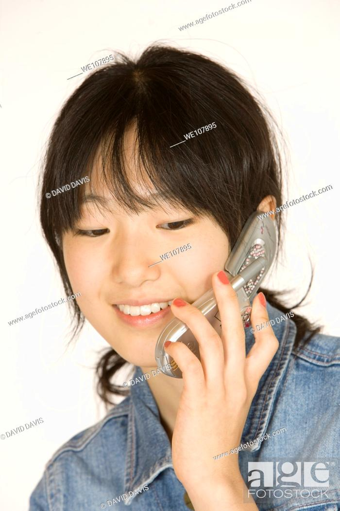 Stock Photo: Portrait of a beautiful Asian teenager talking on a cell phone on a white background.